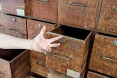 打开老被困扰的木内阁的抽屉精神病学的手 库存照片