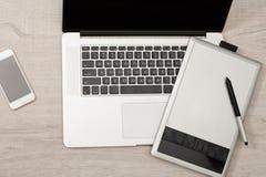 打开膝上型计算机、图形输入板和巧妙的电话在一张轻的桌上,顶视图 免版税库存照片