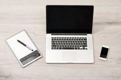打开膝上型计算机、图形输入板和巧妙的电话在一张轻的桌上,顶视图 库存图片