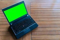 打开膝上型计算机,有说谎在桌上的绿色屏幕的笔记本 免版税库存照片