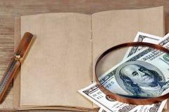 打开葡萄酒笔记薄和一百元钞票在扩大化的gl下 免版税库存图片