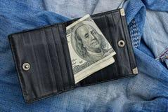 打开蓝色长裤的黑皮革钱包基于 免版税库存图片