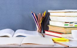 打开课本和精装书堆积与在桌上的铅笔 库存照片
