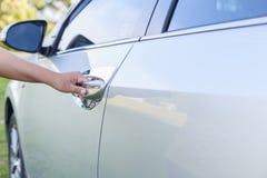 打开车门的妇女手 免版税库存图片