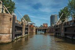打开运河水门、桥梁和大厦在晴朗的蓝天下在阿姆斯特丹 免版税库存图片