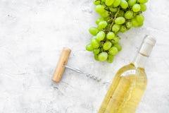 打开酒概念 在玻璃瓶的在灰色背景顶视图的白葡萄酒在葡萄附近和拔塞螺旋复制 免版税图库摄影