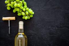 打开酒概念 在玻璃瓶的在黑背景顶视图的白葡萄酒在葡萄附近和拔塞螺旋复制 库存照片