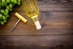 打开酒概念 在玻璃瓶的白葡萄酒在葡萄和拔塞螺旋附近在黑暗的木背景顶视图 图库摄影