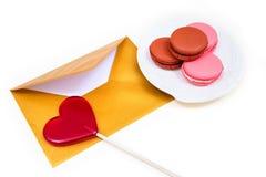 打开金信封、棒棒糖以心脏的形式和macarons 库存照片