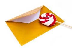 打开金信封和棒棒糖 库存图片