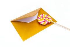 打开金信封和棒棒糖 免版税库存照片
