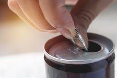 打开铁罐头的手 能与可乐饮料  免版税库存照片