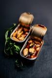 打开锡罐与保存在黑背景的食物 淡菜 免版税库存图片