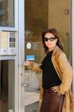 打开门的外套和太阳镜的女商人对办公室 免版税库存照片