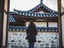 打开门的夹克的一名妇女在好天气的南山谷韩屋村 库存图片