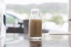 打开非常小葡萄酒减速火箭的玻璃瓶与牛奶ins的牛奶 库存照片
