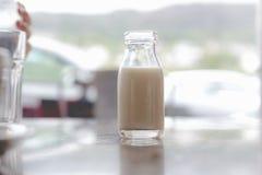 打开非常小葡萄酒减速火箭的玻璃瓶与牛奶ins的牛奶 免版税库存图片