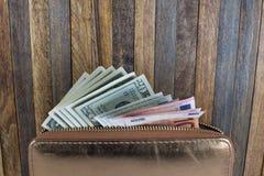 打开非常突出在木背景的钱包和金钱 库存照片