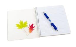 打开练习簿、蓝色笔和黄色和红色叶子 库存照片