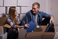 打开移动的箱子的年轻夫妇 库存照片