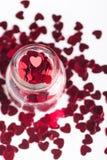 打开玻璃瓶子充满在白色的许多红色一点心脏 免版税库存图片