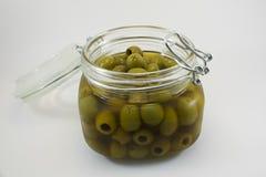 打开玻璃瓶子在白色背景的橄榄 免版税库存图片