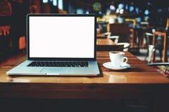 打开说谎在咖啡馆酒吧内部的一张木桌上的便携式计算机和咖啡 免版税库存照片