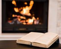 打开说谎在壁炉附近的书 免版税图库摄影