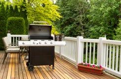 打开BBQ烹饪器材和被装瓶的啤酒在室外雪松露台 库存照片