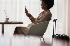 打录影电话的女实业家在机场休息室 免版税库存照片