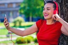 打录影电话的年轻微笑的妇女通过智能手机和headpho 免版税库存照片