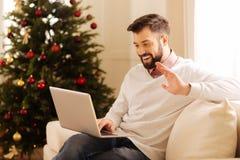 打录影电话的愉快的人在有圣诞树的屋子里 免版税库存图片
