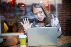 打录影电话的愉快的女孩在膝上型计算机 免版税图库摄影