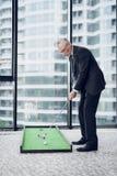 打微型高尔夫球的一个可敬的年长人在办公室 他准备触击 免版税库存照片