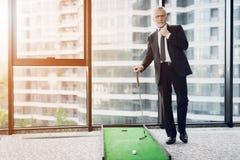 打微型高尔夫球的一个可敬的年长人在办公室 他准备触击 图库摄影