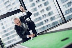 打微型高尔夫球的一个可敬的年长人在办公室 他在打击前投入球 免版税库存照片
