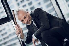 打微型高尔夫球的一个可敬的年长人在办公室 他微笑并且看小小高尔夫球路线 免版税库存照片