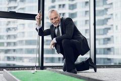 打微型高尔夫球的一个可敬的年长人在办公室 他微笑并且看小小高尔夫球路线 免版税图库摄影