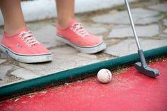 打微型高尔夫球的孩子的脚 免版税库存图片