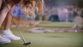 打微型高尔夫球的年轻女人户内 在框架的腿 股票录像