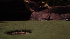 打微型高尔夫球的年轻女人 在框架的腿 r 在孔的射击球 股票视频