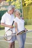 打微笑的网球的夫妇 免版税库存图片