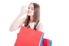 打手势一个完善的标志的愉快的shopaholic女孩画象  免版税图库摄影