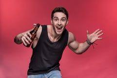 打手势与啤酒瓶和微笑对照相机的年轻人 免版税图库摄影
