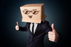 打手势与在他的头的一个纸板箱的商人有兴高采烈的面孔的 库存图片
