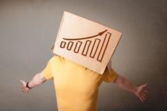 打手势与在他的头的一个纸板箱的年轻人有diagra的 免版税图库摄影