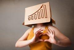 打手势与在他的头的一个纸板箱的少妇有diag的 免版税库存图片