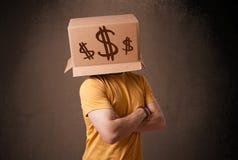 打手势与在他的头的一个纸板箱的年轻人有美元的 免版税库存图片