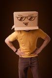 打手势与在他的头的一个纸板箱的年轻人有面带笑容的 库存图片