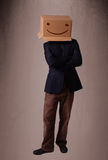 打手势与在他的头的一个纸板箱的年轻人有面带笑容的 库存照片